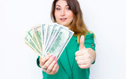 Happy smiling businesswoman wearing in green jacket with thumbs up gesture and money. Closeup portrait super happy excited success Royalty Free Stock Photos
