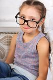 Happy smiling calm kid girl in eyeglasses looking and thinking a. Bout with grimacing fun face. Closeup portrait Stock Images