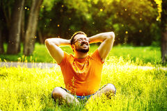 A happy smiling carefree man is sitting on green grass and foldi. Ng arms behind head at sunny summer day at park background. Concept of wellbeing and healthy Royalty Free Stock Photos