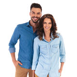 Happy smiling casual couple standing with hands in pockets Stock Images