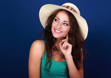 Happy smiling casual makeup woman in summer hat thinking and loo. King on bright blue background Stock Photos