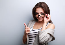 Happy smiling casual woman in glasses showing thumb up Stock Photos