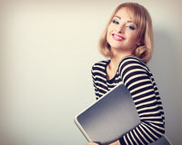 Happy smiling casual woman holding in hand laptop. With empty copy space. Vintage toned portrait Royalty Free Stock Photography