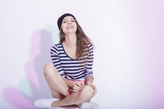 Happy Smiling Caucasian Brunette in Hat and Striped Shirt Posing in Studio Royalty Free Stock Photos