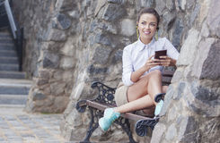 Happy Smiling Caucasian Brunette Woman With Headphones Relaxing on Bench Royalty Free Stock Photos
