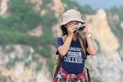 Happy smiling caucasian children asian girl backpack and  holding camera for take a photo check in on mountain. Royalty Free Stock Image