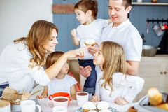 Happy smiling caucasian family having breakfast in the kitchen. stock images