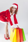 Happy Smiling Caucasian Ginger Santa Helper Girl with Colorful S. Hopping Bags. Posing Against White Background. Vertical Image Orientation royalty free stock image