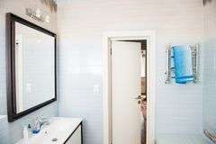 Happy smiling little boy looks into bright blue white bathroom royalty free stock image