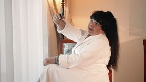 Happy, smiling Caucasian senior woman taking a selfie photo while sitting near a large panoramic window in a white terry. Robe. The concept of using gadgets by stock video