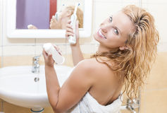 Happy Smiling Caucasian Woman With Modern Electric Toothbrush in Bathroom Stock Image