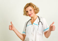 Happy smiling cheerful female doctor with thumbs up gesture Stock Image