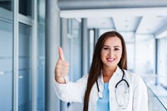 Happy smiling cheerful female doctor with thumbs up gesture. While standing at indoors Stock Images
