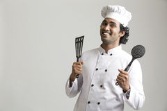 Happy smiling chef holding kitchen utensil Stock Image