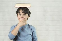 Happy and smiling child with books on head royalty free stock photos