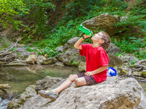 Happy smiling child boy drinking water on forest river back stock photo