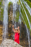 Happy smiling child boy on waterfall background Stock Photos