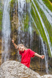 Happy smiling child boy on waterfall background Royalty Free Stock Images