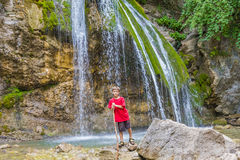 Happy smiling child boy on waterfall background Royalty Free Stock Image