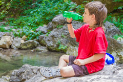 Happy smiling child boydrinking water on forest river back Stock Image