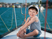 Happy smiling child captain on luxury yacht in a sea cruise stock image