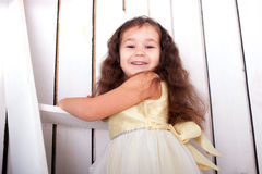 Happy smiling child climbing on ladder up. The white stairs closeup. Bottom view Royalty Free Stock Photos
