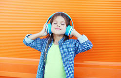 Happy smiling child enjoys listens to music in headphones over colorful orange Royalty Free Stock Photography