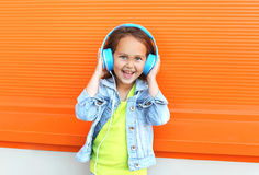 Happy smiling child enjoys listens to music in headphones Stock Photography