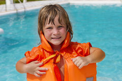 Happy smiling child girl in inflatable life-jacket. Young happy smiling child girl in inflatable life-jacket swimming in pool Royalty Free Stock Images