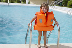 Happy smiling child girl in inflatable life-jacket. Young happy smiling child girl in inflatable life-jacket swimming in pool Stock Photo