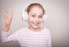 Happy smiling child girl listening music in white headphones. Stock Photos