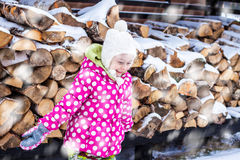 Happy smiling child girl looking at snow outdoor during winter Stock Photography