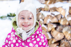 Happy smiling child girl looking at snow outdoor during winter Royalty Free Stock Photo