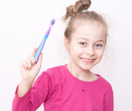 Happy smiling child girl in pyjamas with toothbrush - bedtime. Close up portrait of happy smiling five years old caucasian blond child girl in pyjamas holding Stock Photos