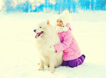 Happy smiling child hugging white Samoyed dog winter Stock Photo