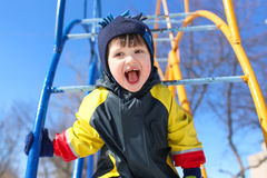 Happy smiling child in overall on climber in winter Royalty Free Stock Images
