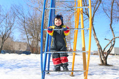 Happy smiling child in overall plays in winter Stock Photos