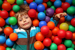 Happy smiling child playing in coloured balls. Smiling young child playing in coloured ball pit royalty free stock image