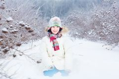 Happy smiling child playing in a snow field Stock Photography