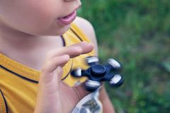 Young schoolboy holding popular fidget spinner toy - close up portrait. Happy smiling child playing with Spinner. Happy smiling child playing with Spinner Royalty Free Stock Photos