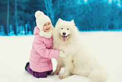 Happy smiling child playing with white Samoyed dog on snow in winter Royalty Free Stock Photos