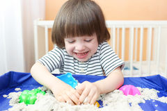 Happy smiling child plays kinetic sand at home Stock Images