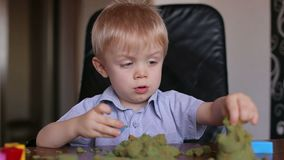 Little boy playing at home with kinetic sand. stock video