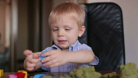 Happy smiling child plays kinetic sand at home. stock video