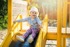 Happy smiling child on slider at outdoor playground Stock Image