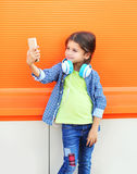 Happy smiling child taking picture self portrait on smartphone in city Royalty Free Stock Image