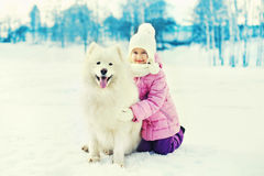 Happy smiling child with white Samoyed dog playing on snow in winter Royalty Free Stock Images