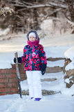 Happy smiling child in winter clothes stands with stick full length Royalty Free Stock Image