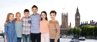 Happy smiling children hugging over london. Childhood, travel, tourism, friendship and people concept - happy smiling children hugging over london city Stock Images