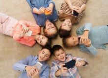 Happy smiling children lying on floor in circle Stock Image
